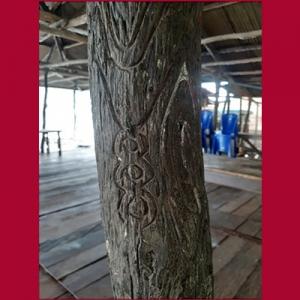 Ukiran gelang pada tiang rumah di Papua